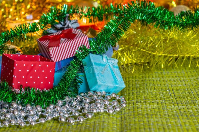 Bunte kleine Geschenkboxen mit Geschenken unter Weihnachtslametta und glänzende Spielwaren und Dekorationen stockbilder