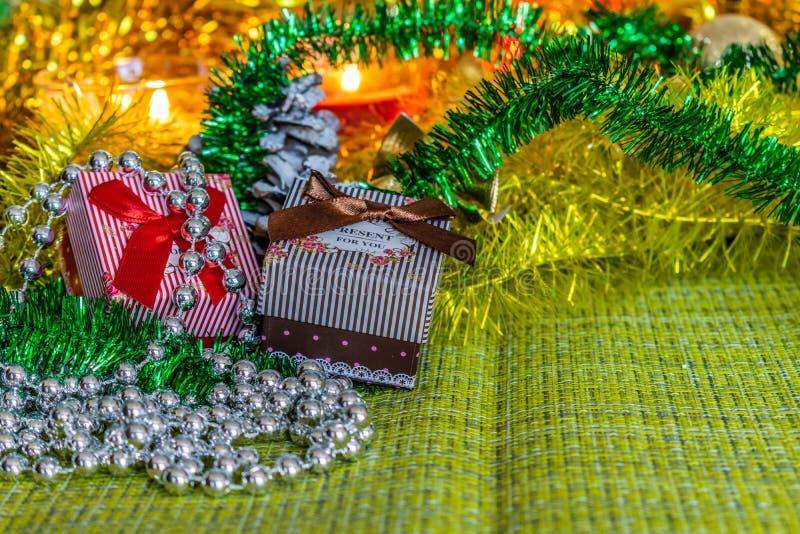 Bunte kleine Geschenkboxen mit Geschenken unter Weihnachtslametta und glänzende Spielwaren und Dekorationen stockfotografie