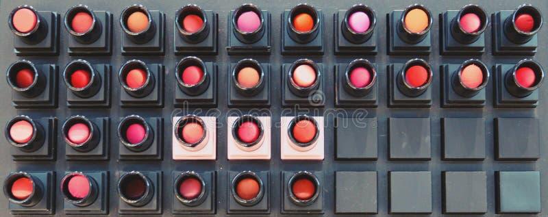 Bunte Lippenstiftprüfvorrichtung auf Regalen für Hintergrund stockfotografie