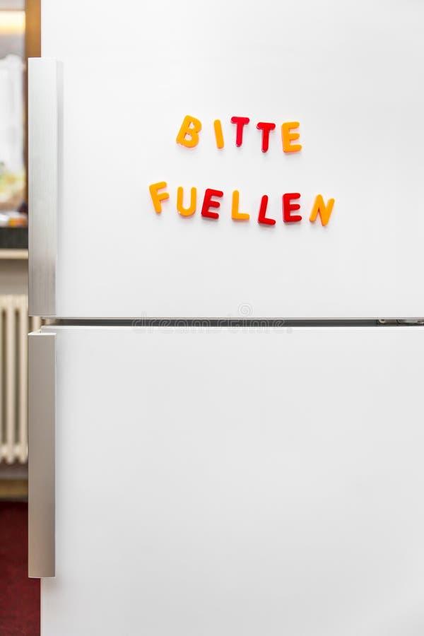Bunte Magnetbuchstaben mit deutschem Text, füllen bitte den Kühlschrank lizenzfreie stockfotos