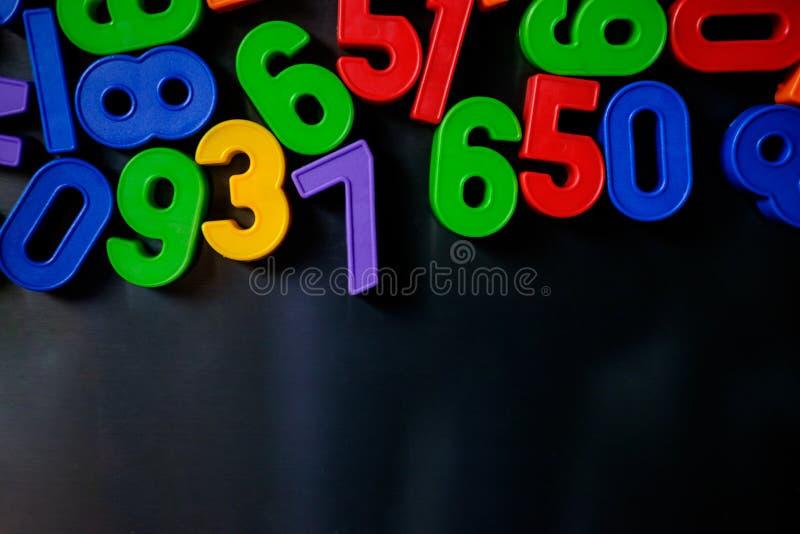 Bunte magnetische Zahlen und Buchstaben auf dem Kühlschrank stockfotos