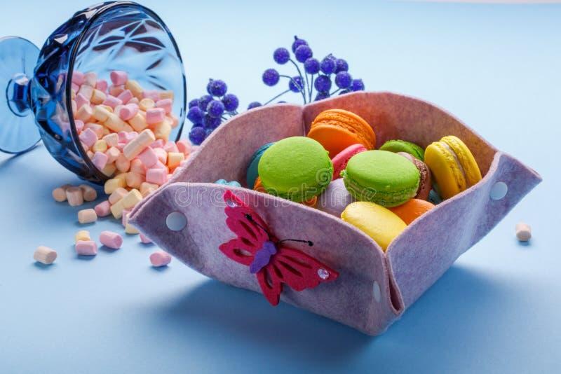 Bunte Makronen über blauem Hintergrund und dem Eibisch, die aus heiterem Himmel Vase gießt Süße Makronen in der Geschenkbox lizenzfreie stockfotos