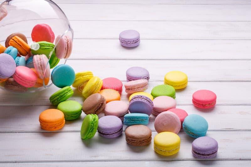 Bunte Makronen oder macarons werden aus dem Kristallvase auf einem weißen Hintergrund heraus gegossen Französische Bonbons lizenzfreie stockfotos