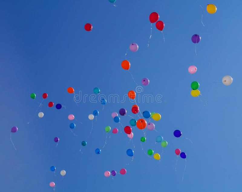 Bunte mehrfarbige aufblasbare Bälle fliegen in einer Luft gegen blauen Himmel des Hintergrundes während des festlichen Festivals lizenzfreie stockfotos