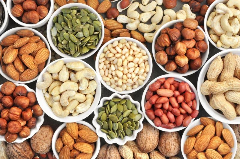 Bunte Mischung von Nuss- und Samenvielzahl: Erdnuss, Acajoubaum, Haselnuss, Mandel, Kiefernnüsse, Walnuss, Kürbiskerne; Imbiss de lizenzfreies stockbild