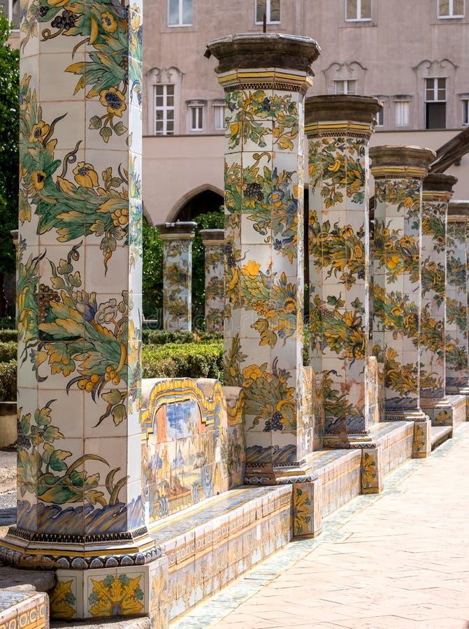 Bunte mit Ziegeln gedeckte Säulen im Klostergarten bei Santa Chiara Monastery herein über Santa Chiara, Neapel Italien stockbild