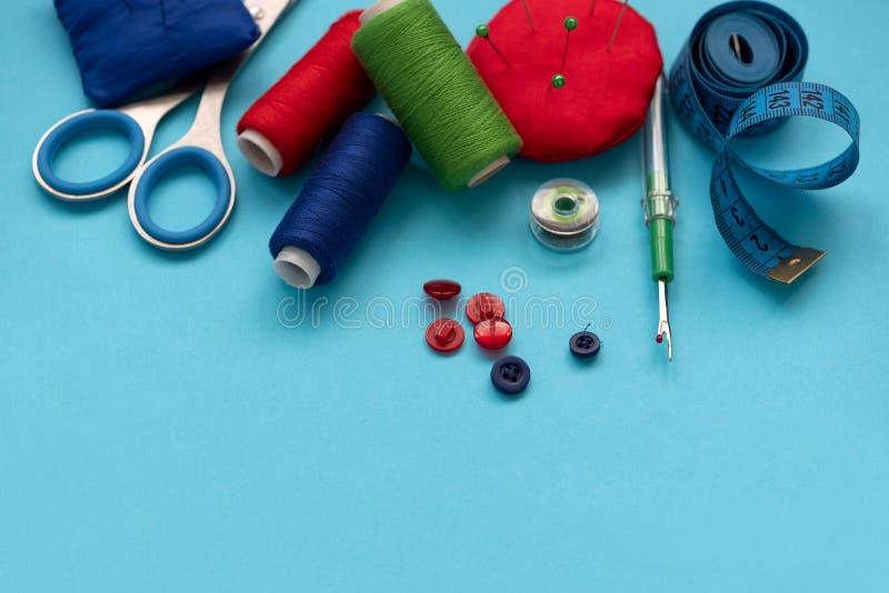 Bunte nähende Zusätze mit Faden, Scheren, Stiften, Gewebe, Knöpfen und nähendem Band auf blauem Hintergrund Beschneidungspfad ein lizenzfreie stockfotos