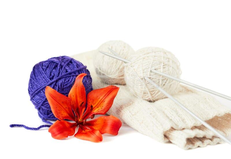 Bunte orange Blume mit lila Schlaufe vor dem weißen Stricken mit Schlaufen von den Threads lokalisiert auf weißem Hintergrund, Ab stockfoto