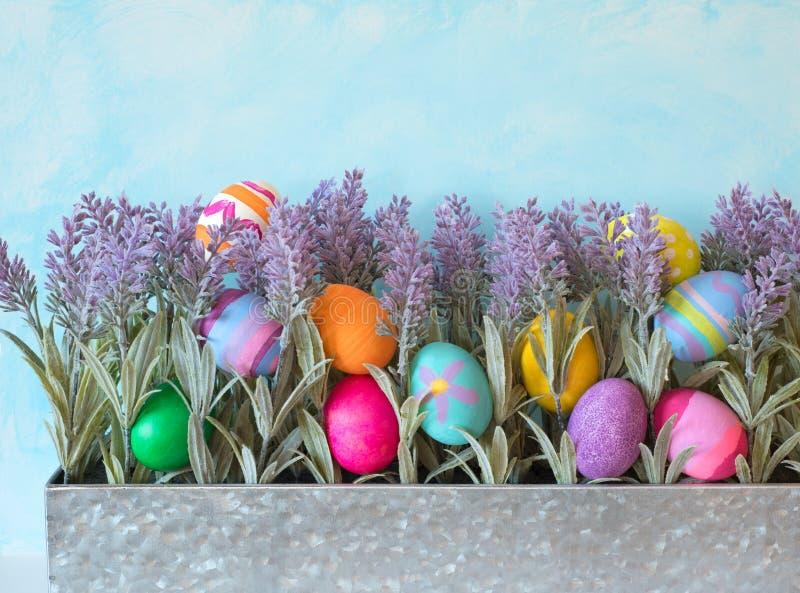 Bunte Osterei-Stillleben-Anzeige mit Lavendel-Blumen im Metallpflanzer gegen blauer Himmel-Hintergrund lizenzfreie stockbilder