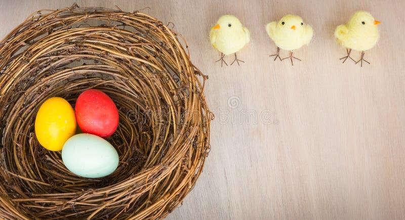 Bunte Ostereier im Nest, Küken auf hölzernem Hintergrund flach stockbilder