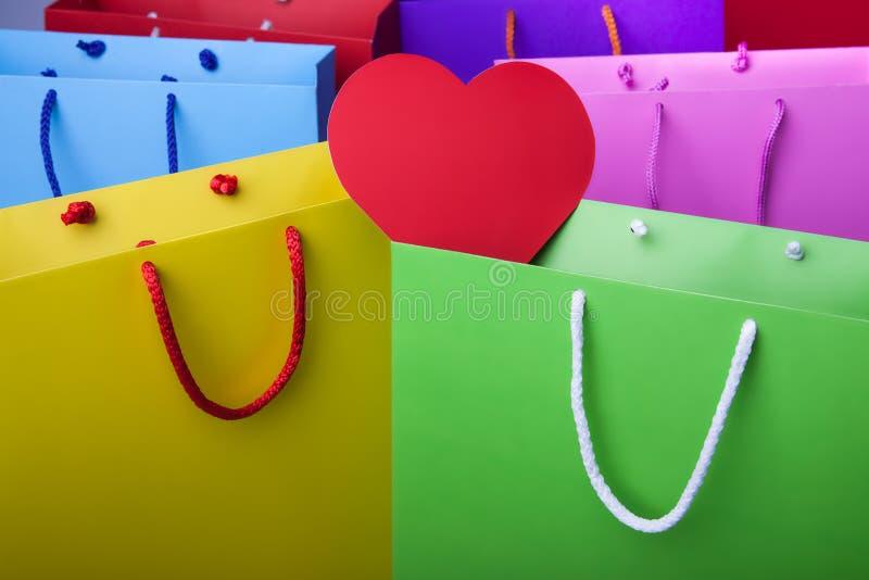 Bunte Papiereinkaufstaschen mit rotem Herzen lizenzfreie stockfotografie