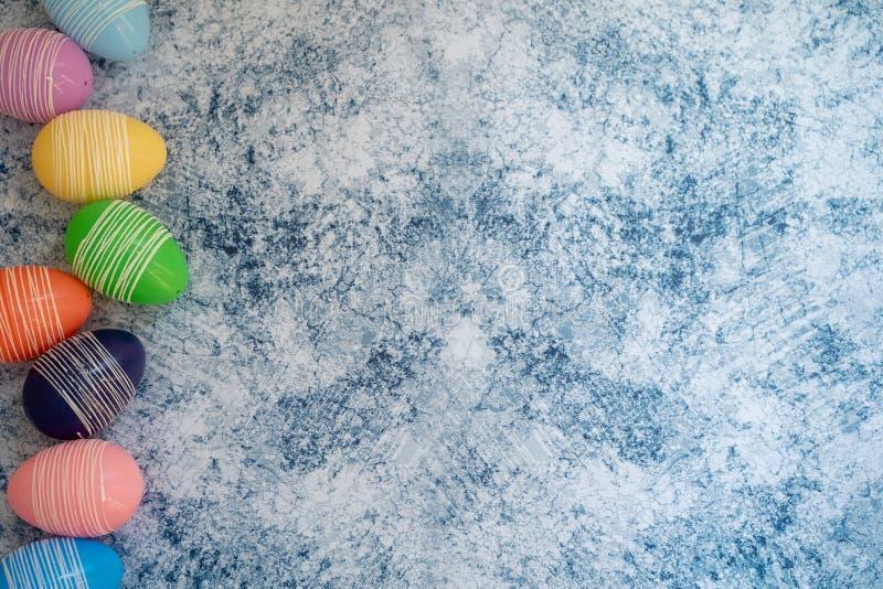 Bunte Pastell-Ostereier auf einem blauen Hintergrund Flatlay legen flach Hintergrund für Frühling stockfotografie