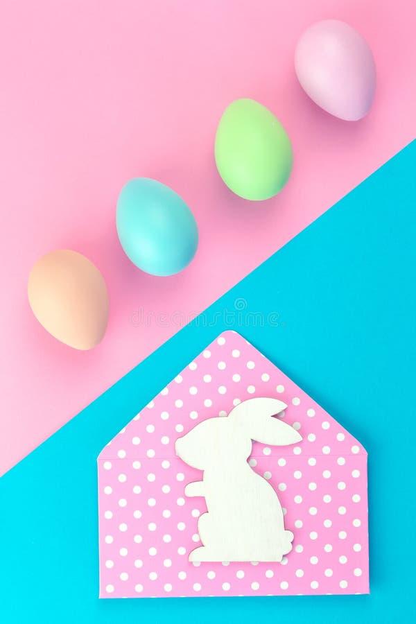 Bunte Pastell-Ostereier auf Rosa und blau mit Häschenumschlag lizenzfreies stockbild