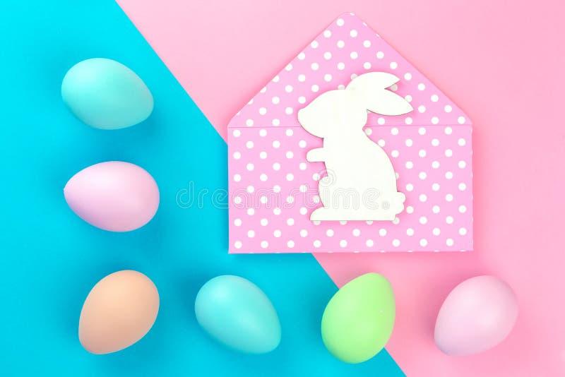 Bunte Pastell-Ostereier auf Rosa und blau mit Häschenumschlag stockbild