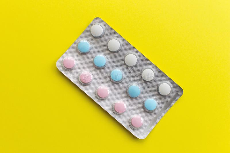 Bunte Pillen der weißen, blauen und rosa Farbe in der Blase auf gelbem einfachem Hintergrund stockfoto