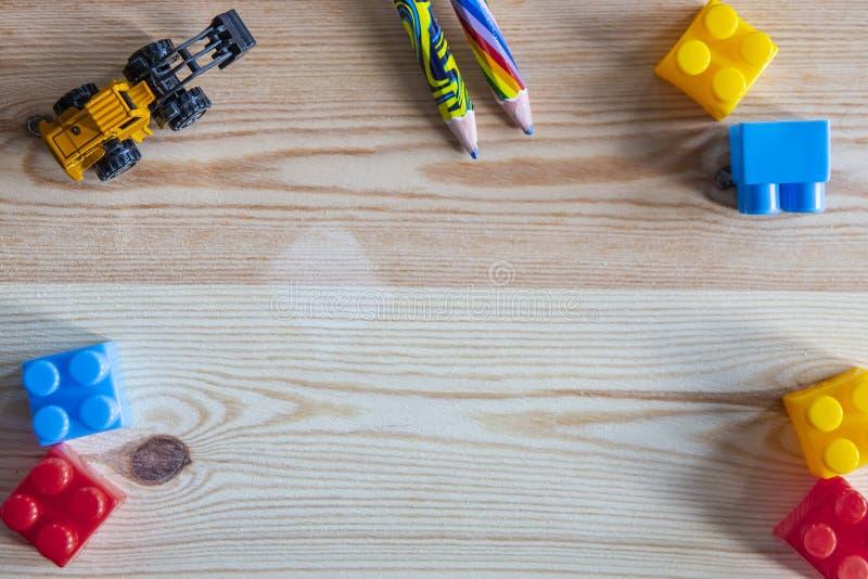 Bunte Plastikblöcke, Zeichenstifte, gelber Spielzeuggräber auf Hintergrund des hölzernen Brettes lizenzfreie stockfotos