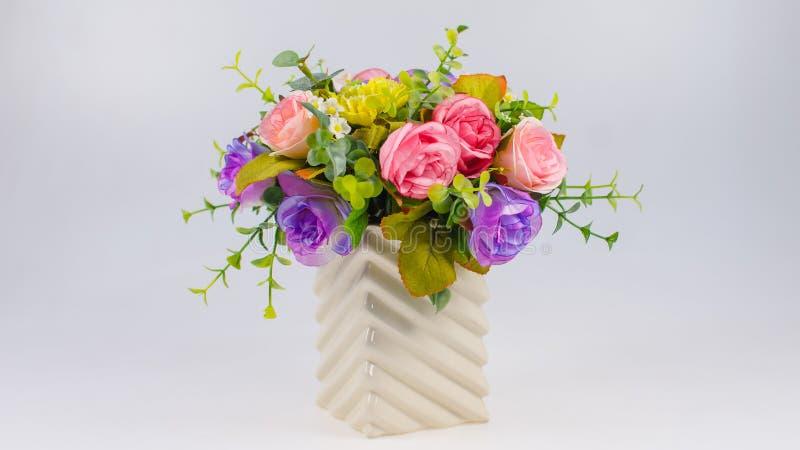 Bunte Plastikblume im Vase auf Weiß lizenzfreies stockbild