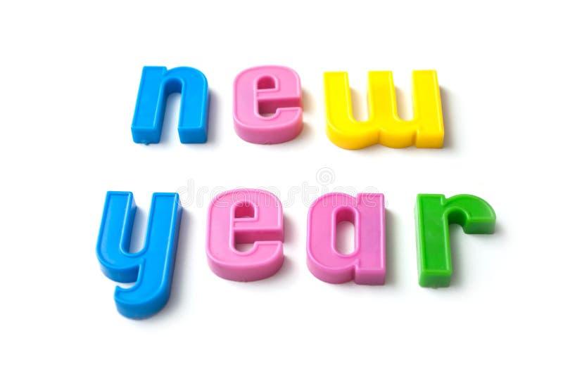 bunte Plastikbuchstaben auf weißem Hintergrund - neues Jahr lizenzfreie stockfotografie