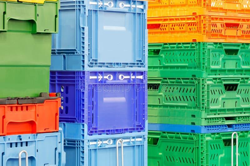 Bunte Plastikkästen stapelten ein nach dem anderen auf Magazinwagen- oder Plattformlaufkatze stockfotografie