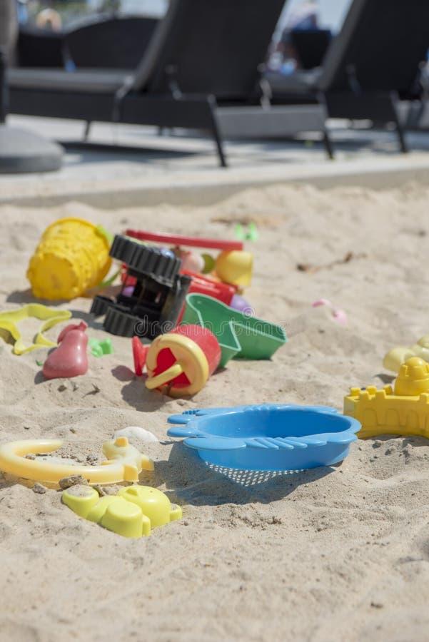 Bunte Plastikspielwaren mit verschiedenen Formen und Arten verließen unbeaufsichtigt auf einem Sandstrand stockfoto