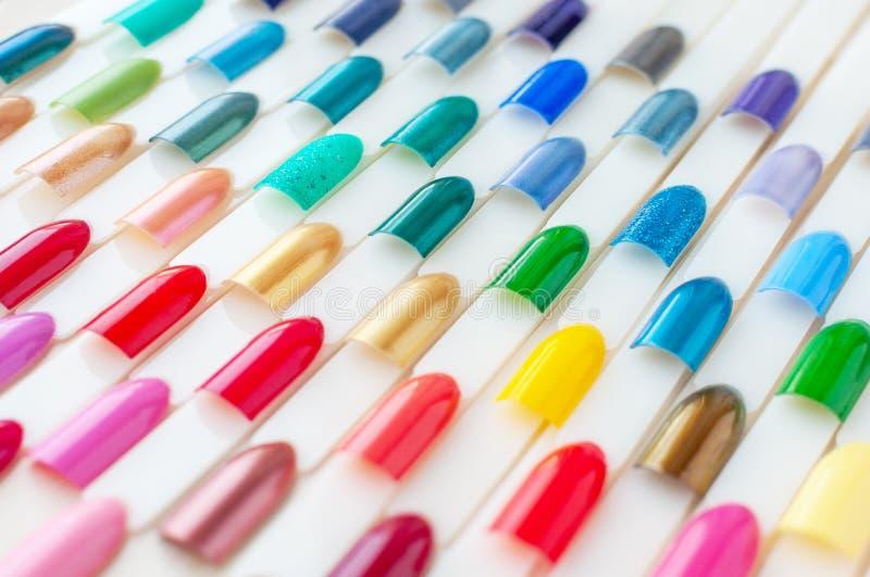 Bunte Proben des Nagellacks in den Regenbogenfarben Stellen Sie von den künstlichen Nägeln ein Beschneidungspfad eingeschlossen stockbilder