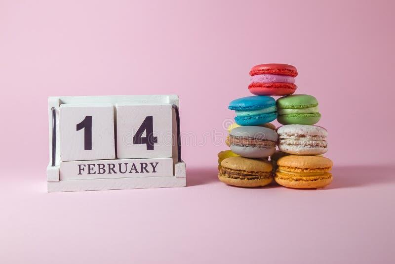 Bunte Pyramide von macarons mit hölzernem Kalender lizenzfreie stockfotografie