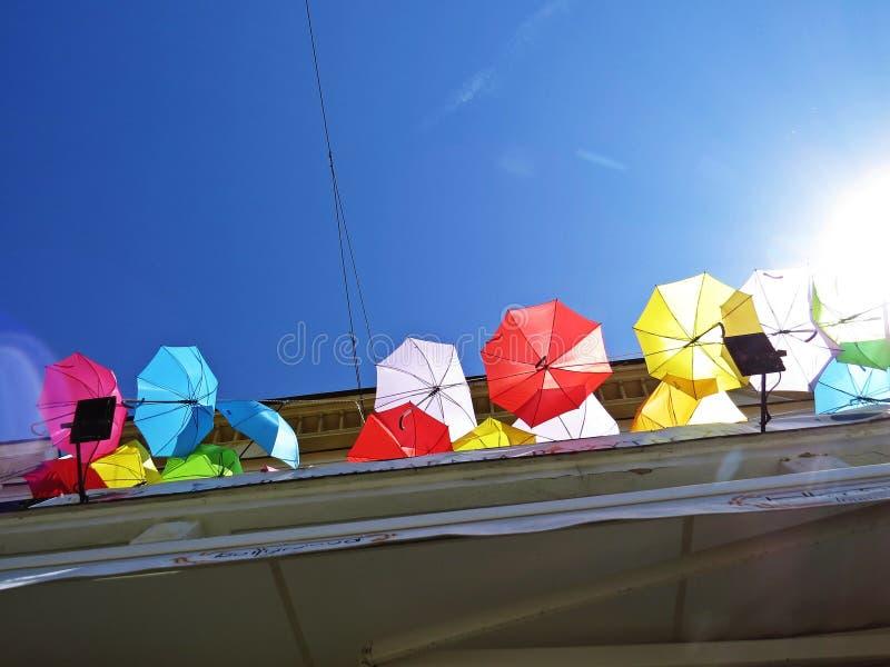 Bunte Regenschirme, die am Balkon mit einem blauen Himmel und am Sun im Hintergrund hängen lizenzfreie stockfotografie