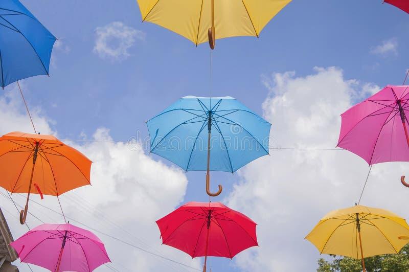 Bunte Regenschirme gegen den Himmel in den Stadteinstellungen lizenzfreie stockfotos