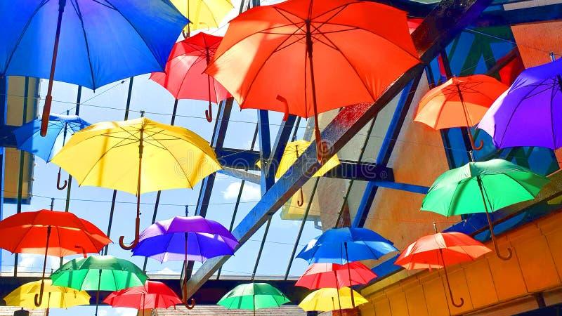 Bunte Regenschirme hängen von einer Glasdecke stockfotos