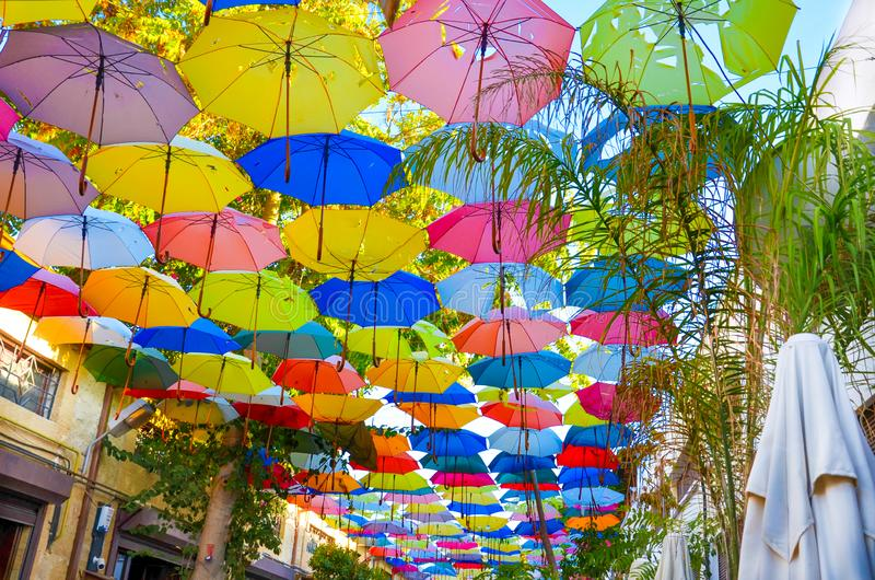 Bunte Regenschirme, welche die Spitze der Straße auf Zyprioten Nikosia verzieren Der Regenschirm dient auch als Schatten und Schu stockbild