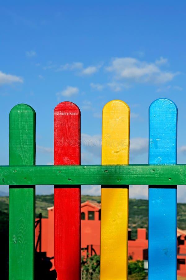 Bunte Reihen des gemalten Holzes auf einem Spielplatzzaun stockbilder