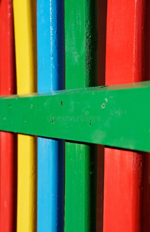 Bunte Reihen des gemalten Holzes auf einem Spielplatzzaun lizenzfreies stockbild