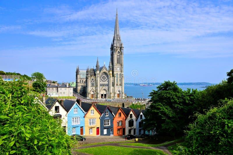 Bunte Reihenhäuser mit Kathedrale im Hintergrund, Cobh, Grafschafts-Korken, Irland lizenzfreie stockfotografie