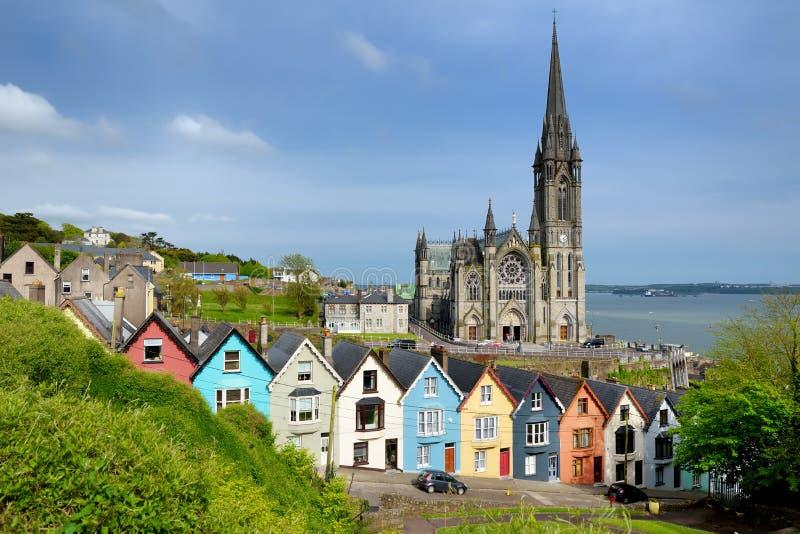 Bunte Reihenhäuser mit Kathedrale St. Colmans im Hintergrund in der Portstadt von Cobh, Grafschafts-Korken, Irland lizenzfreies stockbild