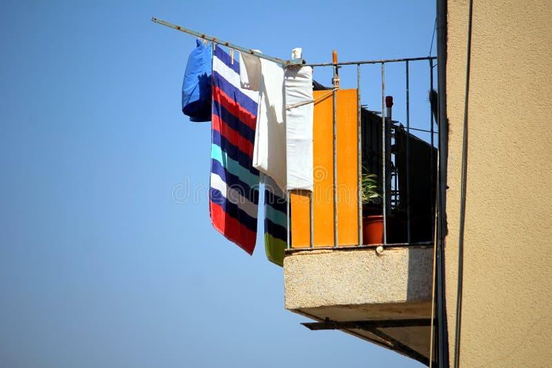 Bunte Reinigung oder Wäscherei, die heraus hängen, um in der Sonne auf einem b zu trocknen lizenzfreie stockfotografie