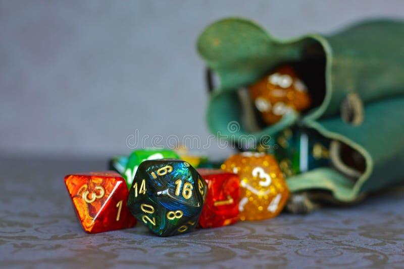 Bunte Rollenspielwürfel, die aus grüne Speicherledertasche herauskommen stockbild