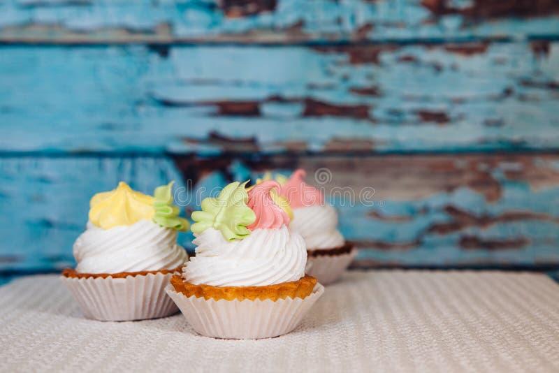 Bunte rosa und gelbe kleine Kuchen auf blauem hölzernem Hintergrund der Weinlese lizenzfreie stockfotografie
