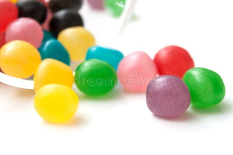 bunte runde Süßigkeiten, die von Glasbehälter O fallen lizenzfreie stockfotos