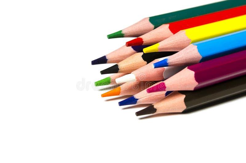 Bunte scharfe Bleistifte liegen auf einem weißen Hintergrund stockfotos