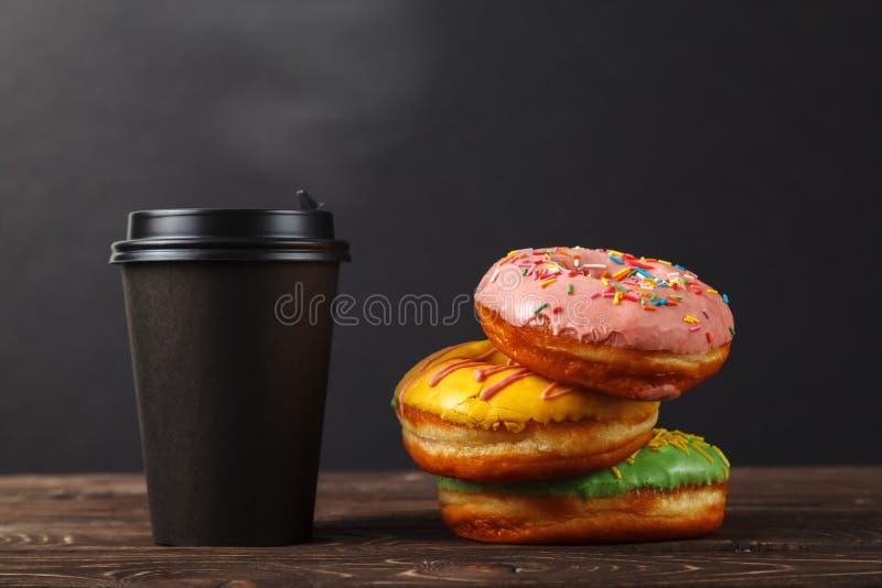 Bunte Schaumgummiringe und Kaffee in einer schwarzen Papierschale auf einem schwarzen Hintergrund Bäckereimenü-Konzept des Entwur stockfoto