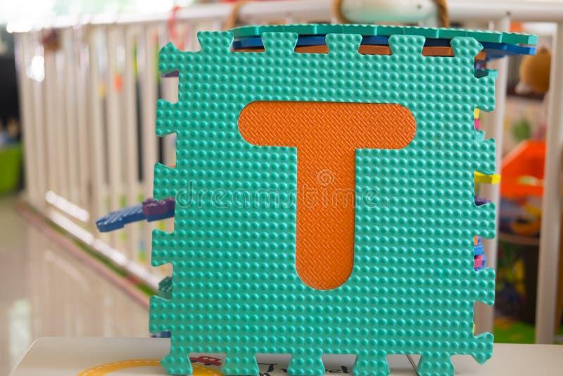 Bunte Schaumpuzzlespielbuchstaben, Alphabet T lizenzfreies stockfoto