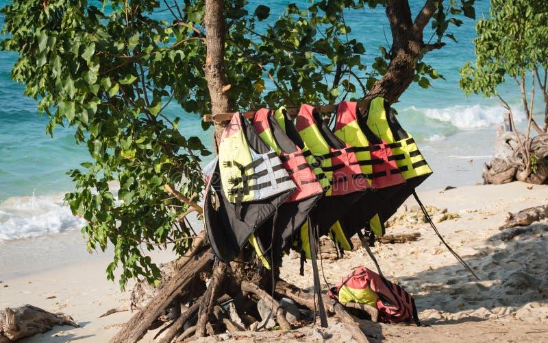 Bunte Schwimmwesten, die an einem Gestell auf einem tropischen Strand hängen stockfotografie
