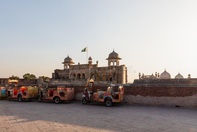 Bunte Selbstrikschas oder tuk-tuks außerhalb des Lahore-Forts bei Sonnenuntergang, Lahore stockbild