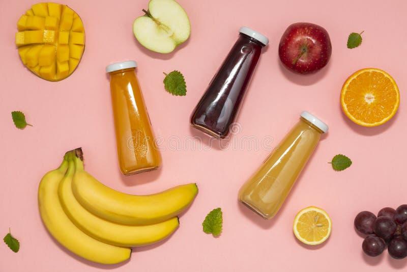 Bunte Smoothies in den Flaschen mit frischen Früchten auf rosa Hintergrund Flache Lage, Draufsicht stockbild