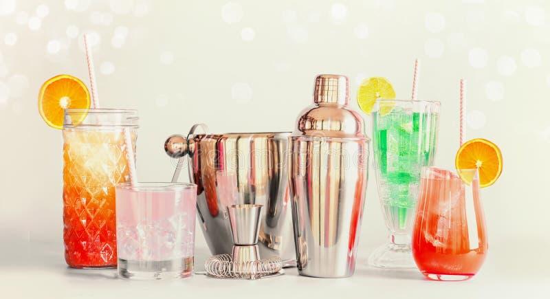Bunte Sommerlongdrinks Bar und Cocktailwerkzeuge in den verschiedenen Gläsern mit den Trinkhalmen und Zitrusfrüchten, die am Lich stockfotografie