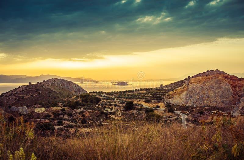 Bunte Sonnenuntergangansicht von Bergen und Meer und drastische Wolken an stockbilder