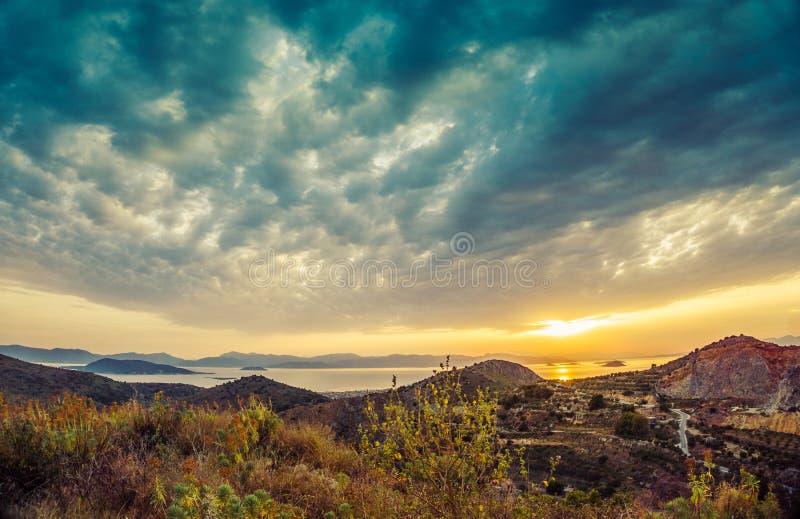 Bunte Sonnenuntergangansicht von Bergen und Meer und drastische Wolken an stockfotografie