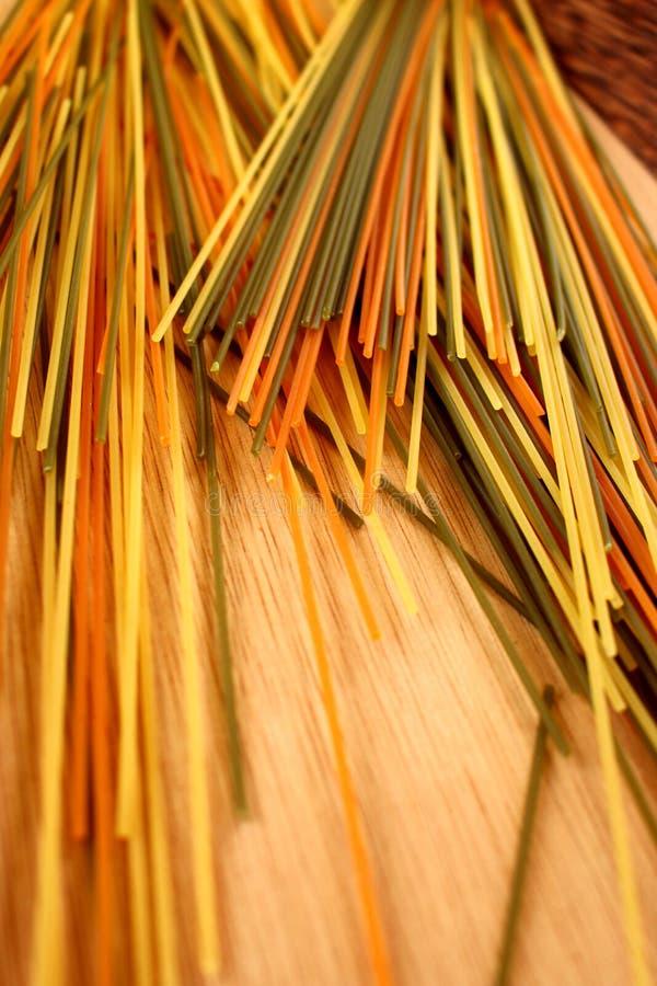 Bunte Spaghettis auf hölzernem Hintergrund lizenzfreies stockfoto