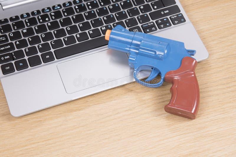 Bunte Spielzeugpistole, die auf einer Laptop-Computer liegt stockfotografie