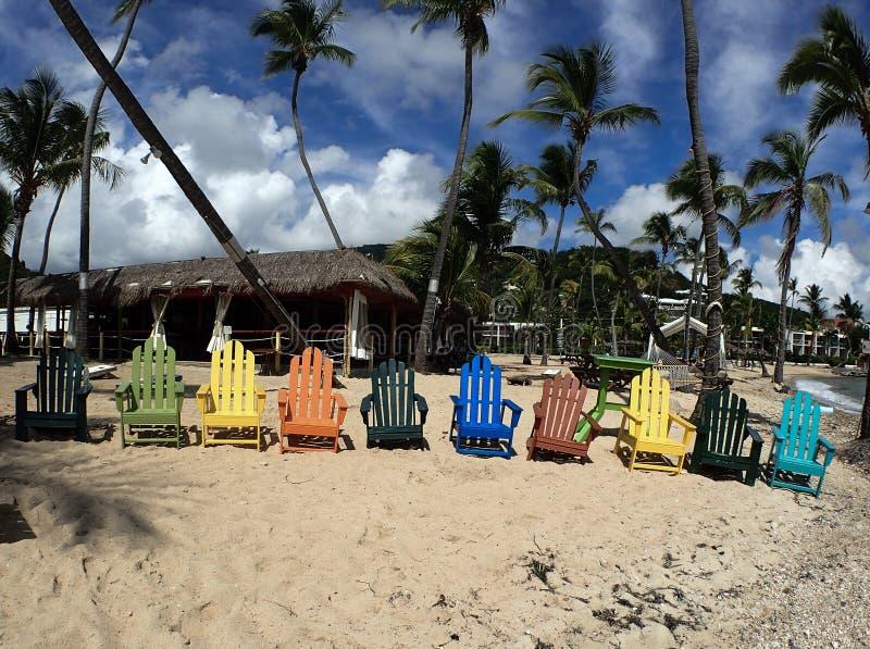 Bunte Strandstühle, Palmen und schöner Sandstrand lizenzfreie stockbilder